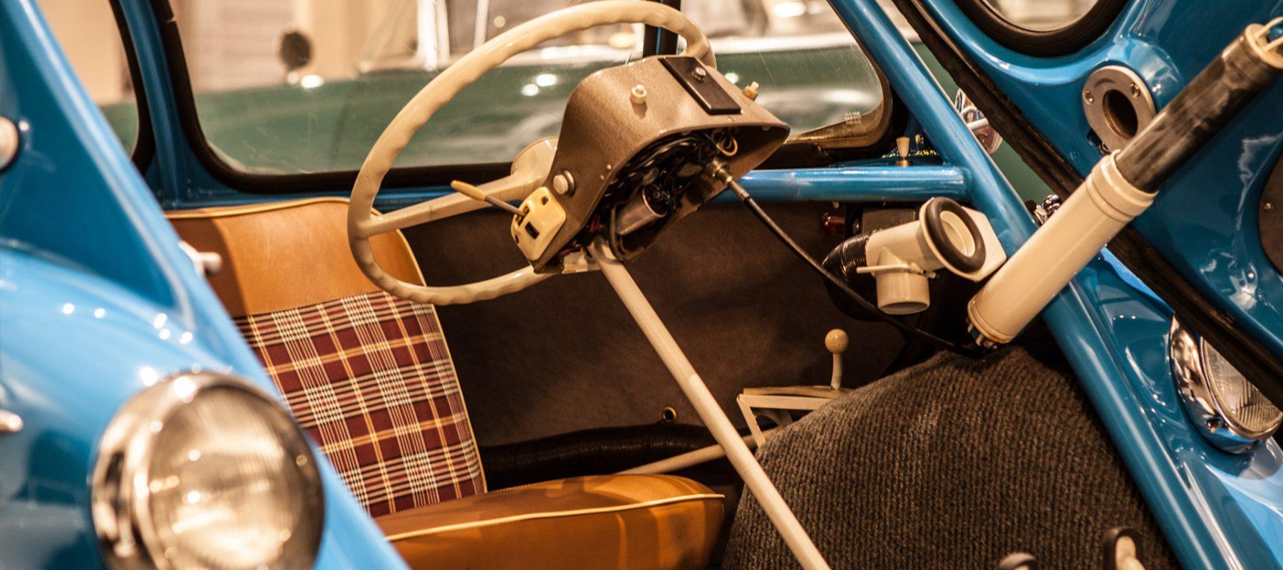Ein Blick in den Innenraum der blauen 1956er Heinkel Kabine, dem dreirädrigen Rollermobil des ehemaligen Flugzeugherstellers Heinkel, zeigt, dass wie bei der BMW Isetta die komplette Front als Tür aufschwingt. Allerdings ist das Lenkrad samt Lenksäule fest montiert und klappt nicht wie bei der Isetta nach vorn. So muss sich der Fahrer erst wie der Beifahrer auf die karierte Sitzbank setzen und dann hinter das Lenkrad rutschen.